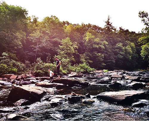 two men climbing on rocks in the river