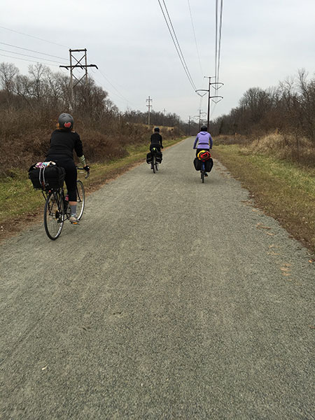 3 women riding bikes down a trail