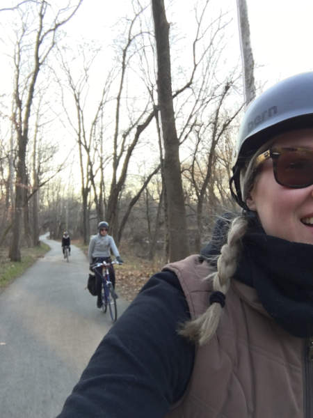 3 women riding on a bike trail